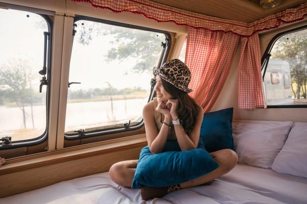 beautiful-young-asian-woman-relaxing-looking-view-motor-home-campsite-evening_49071-3000
