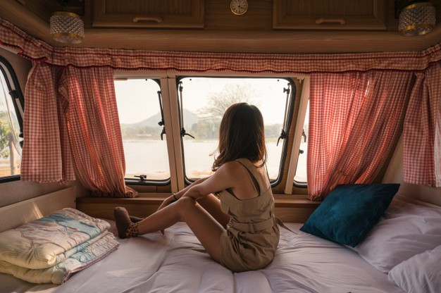beautiful-young-asian-woman-relaxing-looking-view-motor-home-campsite-evening_49071-3001