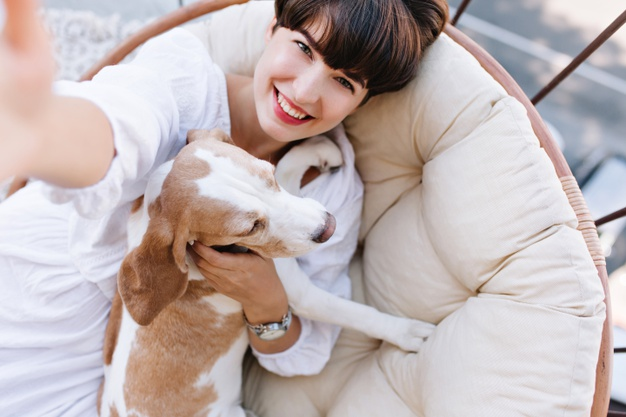 excited-girl-with-short-brown-hair-laughing-while-taking-photo-herself-with-beagle-dog_197531-4860
