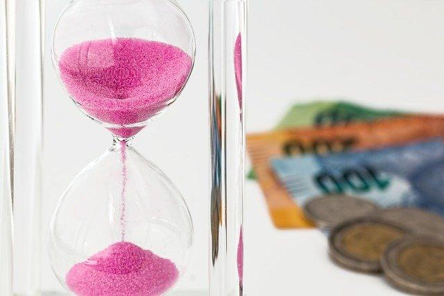 Presýpacie hodiny s ružovým pieskom, za ktorými sú papierové bankovky.jpg