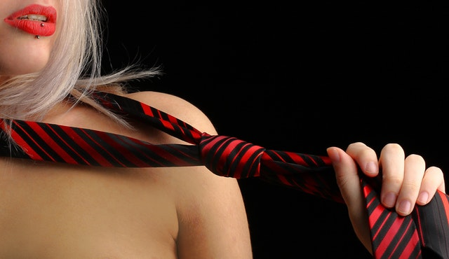 Nahá žena má okolo krku omotanú kravatu
