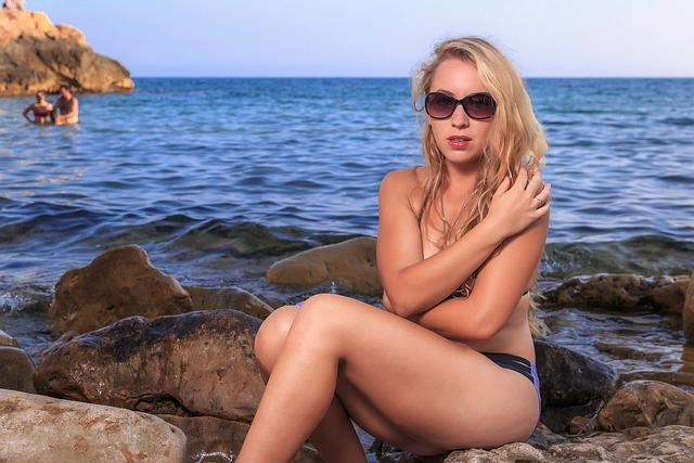 Nahá žena sedí na skalách pri vode
